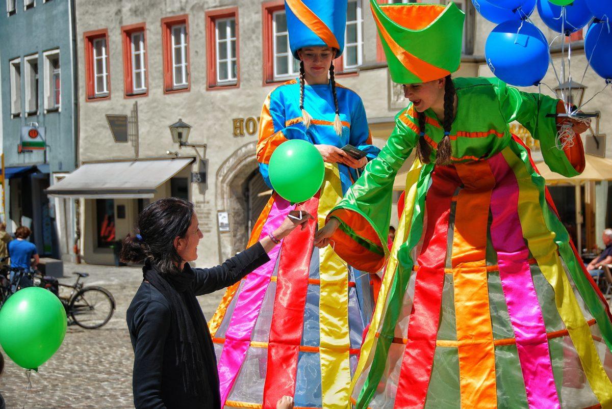 Die Stelzenläufer verteilen im Rahmen der Automesse in Regensburg Luftballons von der Jepsen Sky Bar